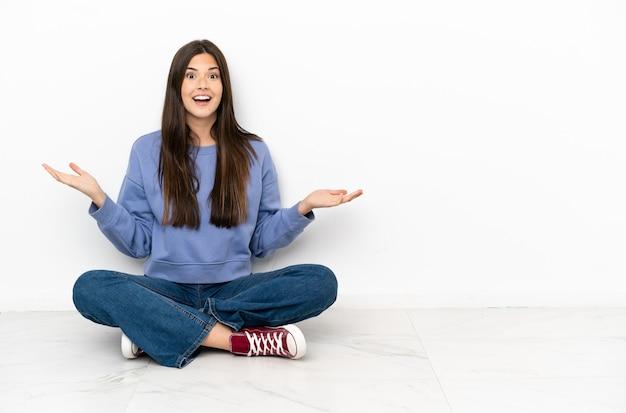 충격 된 표정으로 바닥에 앉아 젊은 여자