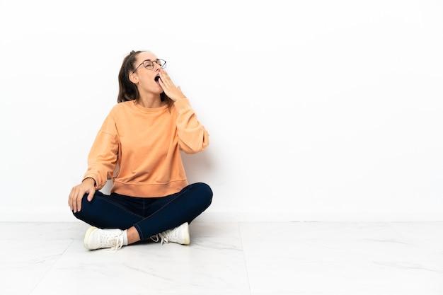 Молодая женщина сидит на полу, зевая и прикрывая широко открытый рот рукой