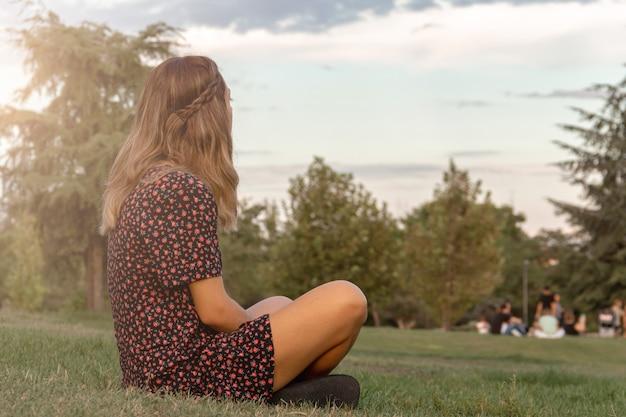 Молодая женщина, сидя на лужайке в парке, глядя на бесконечность. выборочный фокус.