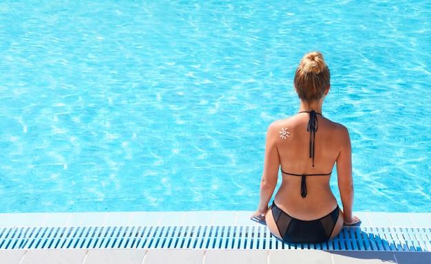 수영장의 난간에 앉아 젊은 여자. 태양 보호. 선크림. 피부와 몸
