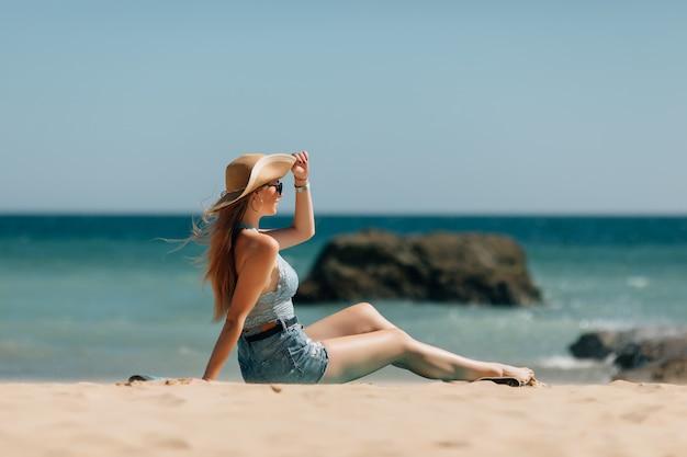 海のビーチに座っていた若い女性