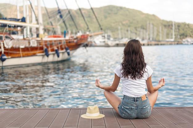 港の海岸に座っている若い女性