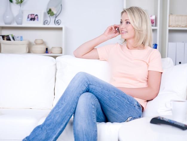 방에 소파에 앉아 전화로 말하는 젊은 여자