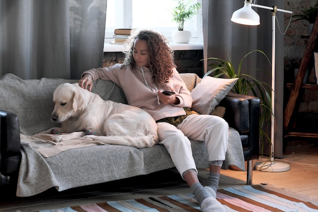 Молодая женщина сидит на диване с мобильным телефоном и гладит собаку в гостиной дома
