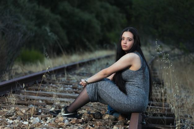 기차 트랙에 앉아 젊은 여자