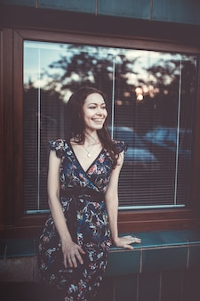 誰かを見て笑っている窓に座っている若い女性