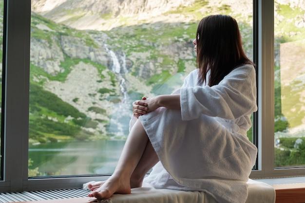 Молодая женщина сидит на подоконнике и наслаждается прекрасным видом