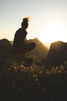 山の頂上に座って、日没時に景色を楽しむ若い女性