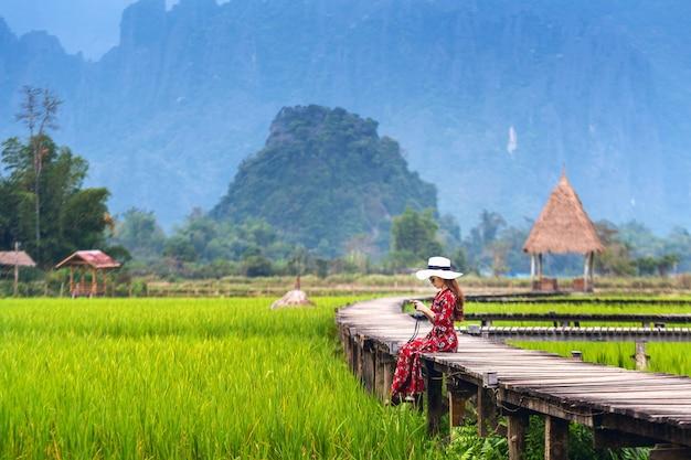Молодая женщина, сидящая на деревянном пути с зеленым рисовым полем в ванг-вьенге, лаос.