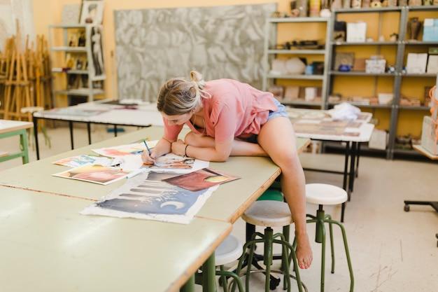 Молодая женщина, сидя на верстаке, делая живопись в мастерской
