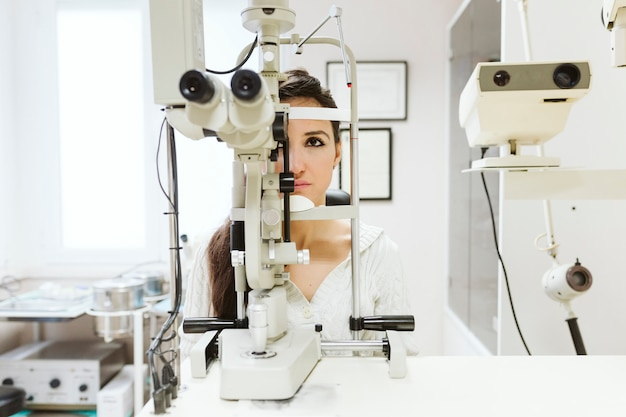 Young woman sitting at ophthalmologist clinic to get her eyes examined by a professional.