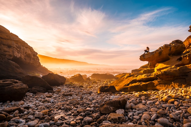 A young woman sitting at the orange sunset on the coast of mount jaizkibel near san sebastian, gipuzkoa. spain