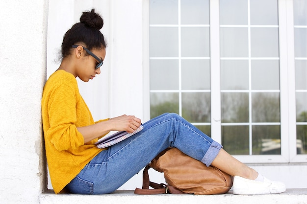 Young woman sitting outdoors and reading a book
