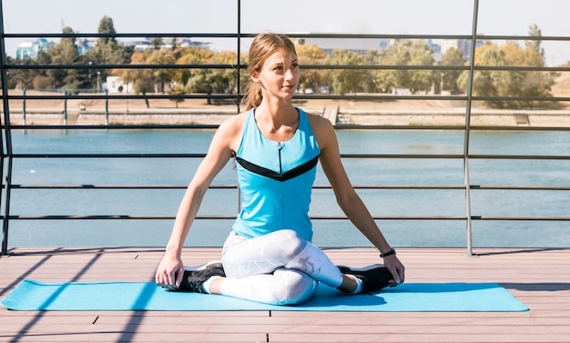 Young woman sitting outside on blue exercise mat practicing exercise near the lake