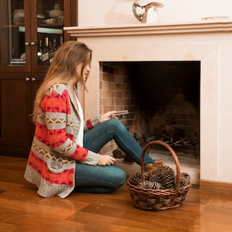 Young woman sitting outside the fireplace with matchbox and pinecone basket