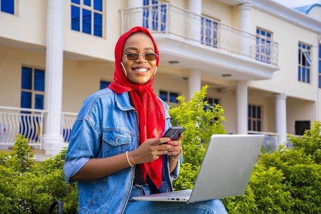 彼女のラップトップと電話で外に座っている若い女性