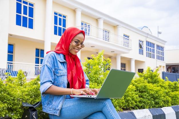 Молодая женщина, сидящая на улице со своим ноутбуком и телефоном