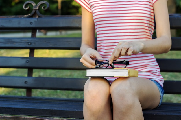 A young woman sitting in the park and holding a book with glasses