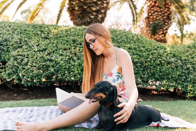Young woman sitting in park with her dog reading book