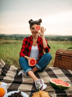 Young woman sitting on plaid, picnic in summer field. romantic junket, happy holiday