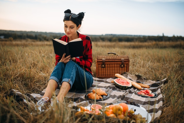 Young woman sitting on plaid and reads book, picnic in summer field. romantic junket, happy holiday