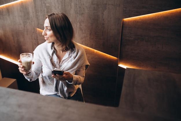 Giovane donna seduta alla reception e bere caffè