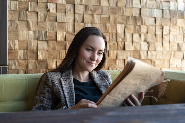 Young woman sitting in a restaurant with a menu in her hands makes a choice of dishes