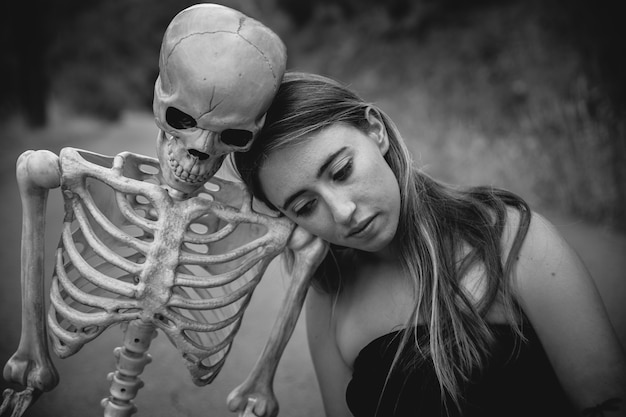 Young woman sitting on road with skeleton and looking down