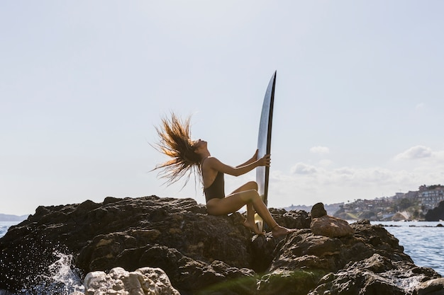 Young woman sitting on rocky sea shore with surfboard and shaking hair