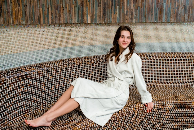 Young woman sitting in sauna and smiling