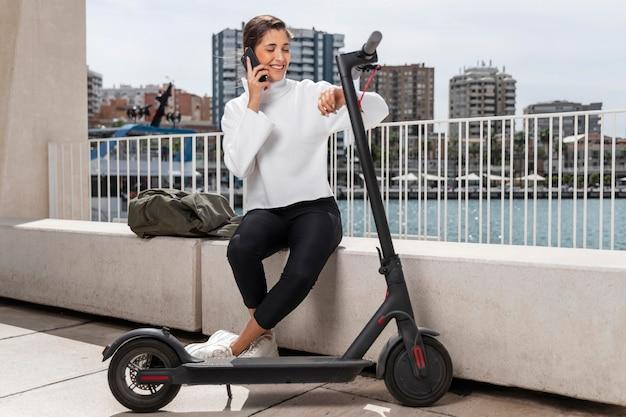 Giovane donna seduta accanto a uno scooter