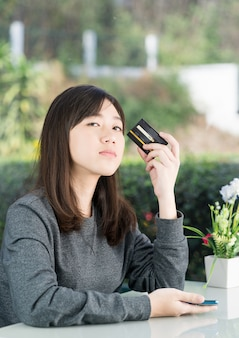 Молодая женщина сидит, показывает кредитную карту и держит смартфон для покупок в интернете, концепция покупок в интернете