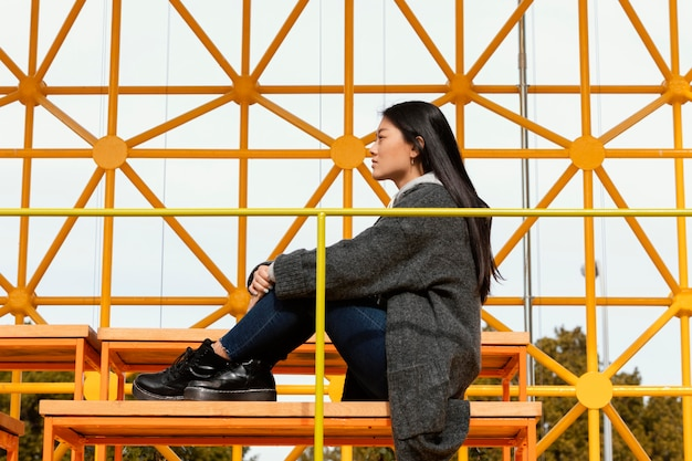 Young woman sitting on site construction bridge