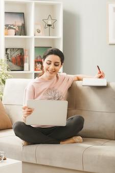 La giovane donna che si siede sul sofà dietro il tavolino da caffè che tiene e il computer portatile usato scrive sul libro in soggiorno