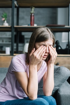 Young woman sitting on sofa having eye pain
