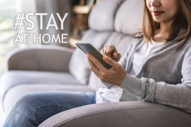 Young woman sitting on sofa at living room and using cell phone at home
