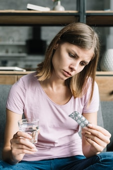 Young woman sitting on sofa looking at pill blister pack