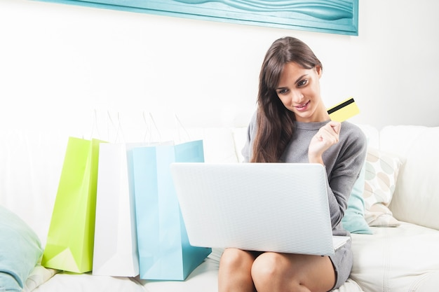 Young woman sitting on sofa shopping online with shopping bags