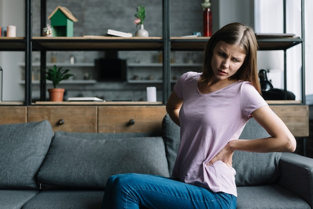 Young woman sitting on sofa suffering from back pain