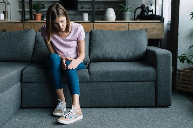 Young woman sitting on sofa suffering from knee pain