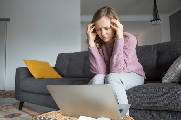 Young woman sitting on sofa with closed eyes, having headache