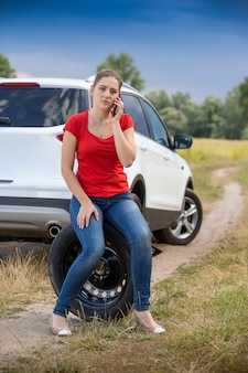 Young woman sitting on the spare tire at roadside and calling for help