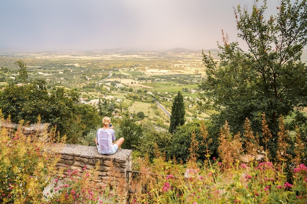 Young woman sitting on the stone fence in medieval hilltop village of gordes provence france
