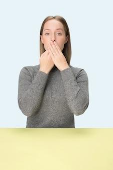 Giovane donna seduta al tavolo che copre la bocca isolata sul blu