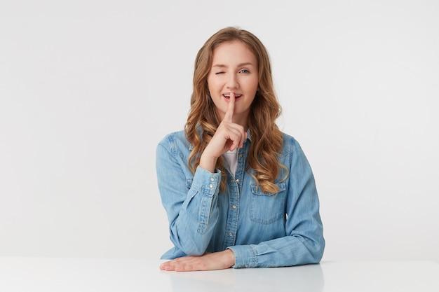 La giovane donna seduta al tavolo, sorridente e ammiccante, dimostra un gesto di silenzio, tenendo un dito indice vicino alla bocca chiede che la privacy sia mantenuta calma, isolata su sfondo bianco.