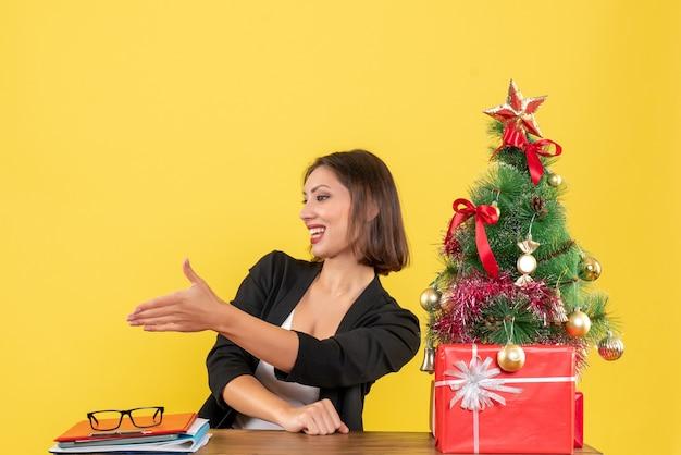 Giovane donna seduta a un tavolo e accogliere qualcuno in tuta vicino all'albero di natale decorato in ufficio su giallo