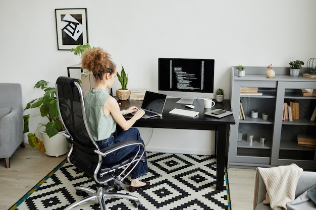 Young woman sitting on the table with computer monitor and working over new software at office