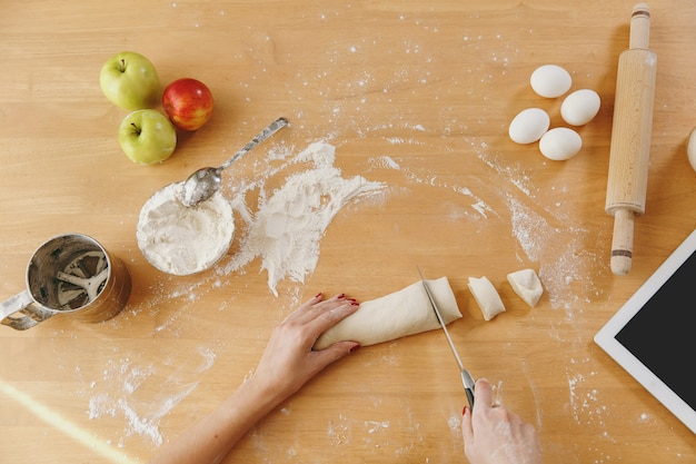 A young woman sitting at a table with tablet, cuts a dough with a knife into pieces at home in the kitchen. cooking home. prepare food. top view.