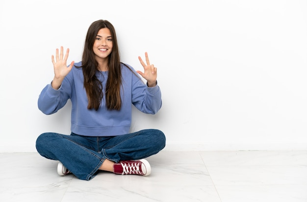 손가락으로 8 세 바닥에 앉아 젊은 여자