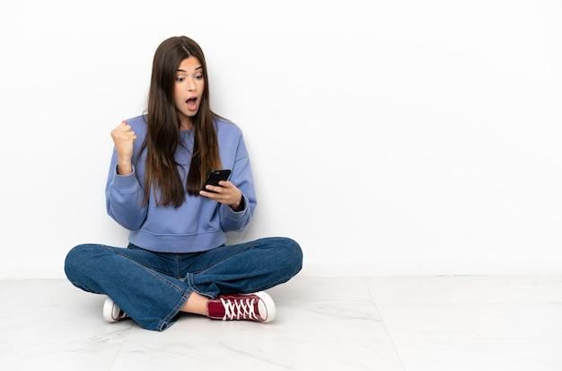 Молодая женщина сидит на полу с удивлением и отправляет сообщение